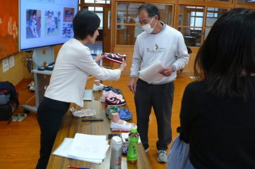 西都市立妻北小学校にて講座終了後の様子。講座でスライドによる解説を行った靴選びのポイントを、見本の靴に触れて確認。